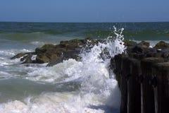 Wellen, die sich waschen, um entlang Schutzwand unterzustützen Lizenzfreies Stockbild