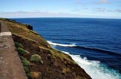 Wellen, die unter Klippe zusammenstoßen Lizenzfreies Stockfoto