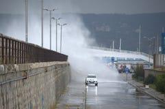 Wellen, die Wellenbrecher und Autos überschwemmen Stockbilder