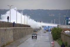 Wellen, die Wellenbrecher und Straße überschwemmen Stockbilder