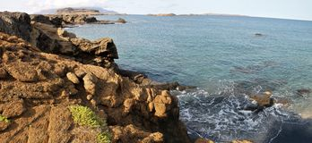 Wellen durch trockene Klippe Lizenzfreie Stockbilder