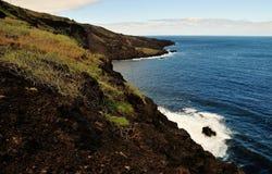 Wellen gegen die vulkanische Küstenlinie Stockbild