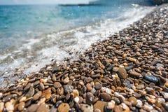 Wellen gespritzt auf dem Pebble Beach Lizenzfreies Stockfoto