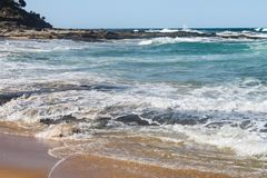 Wellen hetzen auf Ufer über flachen vulkanischen Felsen mit mehr Felsen, die heraus in das Meer hervorstehen lizenzfreie stockbilder