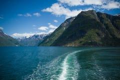 Wellen hinter einem Kreuzschiff auf einem ausgezeichneten Fjord in Norwegen Sonniger Tag Smaragdwasser des Fjords Berge und Himme stockfotos