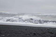Wellen im schönen vulkanischen schwarzen Sand setzen auf den Strand lizenzfreies stockfoto