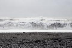 Wellen im schönen vulkanischen schwarzen Sand setzen auf den Strand stockbilder