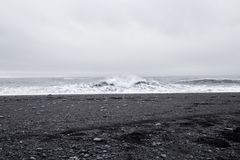 Wellen im schönen vulkanischen schwarzen Sand setzen auf den Strand stockfotos