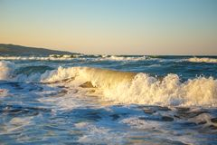 Wellen im Sonnenuntergang schönes Meer mit Wellen und Spray, das Konzept der Reise, eine schöne Strandkarte Stockbild