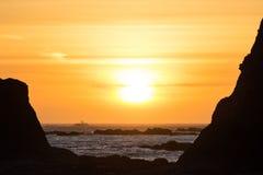 Wellen stoßen gegen die Felsen bei Sonnenuntergang an Rialto-Strand, Washington, US zusammen Stockfotografie