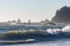 Wellen stoßen gegen die Felsen bei Sonnenuntergang an Rialto-Strand, Washington, US zusammen Stockbild