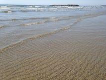 Wellen und geplätscherter Sand Stockfoto