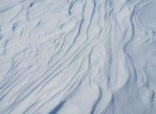 Wellen und Linien geschaffen durch den Wind auf frischem Schnee stockbild