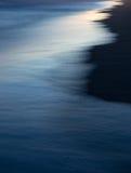 Wellen und Reflexionen auf dem Strand bei Sonnenuntergang. Stockbild