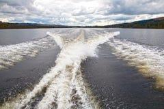 Wellen verließen durch ein Motorboot auf der Loch- Lomondwasseroberfläche Stockfotos
