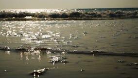 Wellen waschen sich über goldenem Sand auf dem Strand stock video footage
