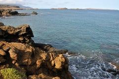 Wellen zertrümmern unter Küstenlinie Stockfotografie