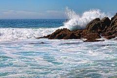 Wellenabbruch über Felsen Stockbild