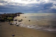 Wellenabbruch auf Felsen und Strand lizenzfreies stockbild