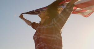 Wellenartig bewegende amerikanische Flagge der Frau auf dem Strand im Sonnenschein 4k stock video