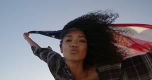 Wellenartig bewegende amerikanische Flagge der Frau auf dem Strand im Sonnenschein 4k stock footage