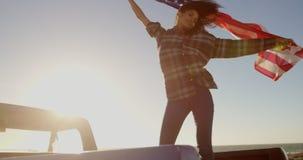 Wellenartig bewegende amerikanische Flagge der Frau auf Kleintransporter am Strand 4k stock footage