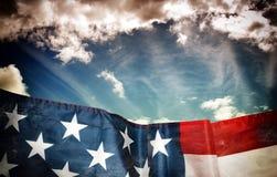 Wellenartig bewegende amerikanische Flagge und Himmel in der dunklen Schmutzart Stockbild