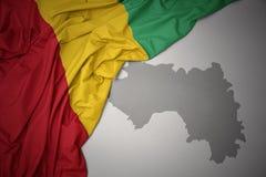 Wellenartig bewegende bunte Staatsflagge und Karte der Guine lizenzfreie abbildung