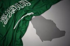 Wellenartig bewegende bunte Staatsflagge und Karte von Saudi-Arabien lizenzfreie stockbilder