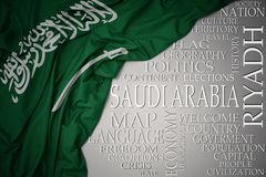 Wellenartig bewegende bunte Staatsflagge von Saudi-Arabien auf einem grauen Hintergrund mit wichtigen Wörtern über Land lizenzfreie stockfotografie
