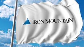 Wellenartig bewegende Flagge mit Iron Mountain-Logo Wiedergabe Editoial 3D Lizenzfreie Stockfotografie