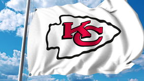 Wellenartig bewegende Flagge mit Kansas City Chiefs-Berufsteamlogo Redaktionelle Wiedergabe 3D Lizenzfreie Stockfotos