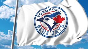 Wellenartig bewegende Flagge mit Toronto Blue Jays-Berufsteamlogo Redaktionelle Wiedergabe 3D Lizenzfreie Stockfotografie