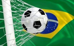 Wellenartig bewegende Flagge und Fußball Brasiliens im Zielnetz Stockfotos