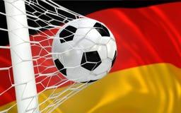 Wellenartig bewegende Flagge und Fußball Deutschlands im Zielnetz Lizenzfreie Stockfotos