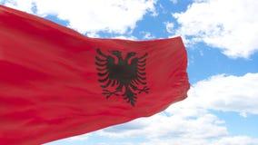 Wellenartig bewegende Flagge von Albanien auf blauem bewölktem Himmel Lizenzfreies Stockfoto