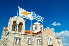 Wellenartig bewegende Flagge von Zypern und von Griechenland mit orthodoxer Kirche auf dem BAC Stockbild