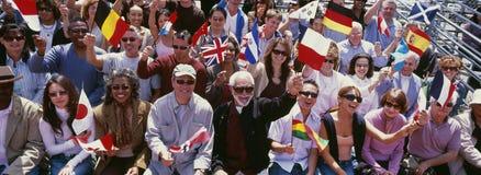 Wellenartig bewegende Flaggen der glücklichen Gruppe von Personen von verschiedenen Ländern Lizenzfreie Stockfotografie