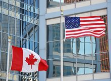 Wellenartig bewegende Flaggen von USA und von Kanada Lizenzfreie Stockfotos