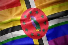 Wellenartig bewegende Flaggenfahne des homosexuellen Stolzes Dominica-Regenbogens Stockfotos