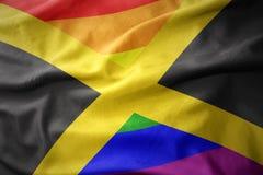 Wellenartig bewegende Flaggenfahne des homosexuellen Stolzes Jamaika-Regenbogens Stockfoto