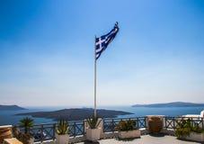 Wellenartig bewegende griechische Flagge auf Betrachtungsplattform in Santorini Lizenzfreie Stockfotos