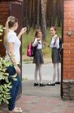 Wellenartig bewegende Hände der jungen Schönheit zu ihren Töchtern, die zur Schule verlassen Lizenzfreie Stockbilder