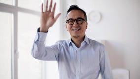 Wellenartig bewegende Hand des glücklichen asiatischen Geschäftsmannes im Büro stock video