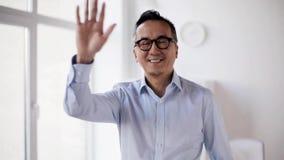 Wellenartig bewegende Hand des glücklichen asiatischen Geschäftsmannes im Büro stock footage