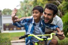 Wellenartig bewegende Hand des Vaters und des Sohns beim Radfahren lizenzfreies stockbild