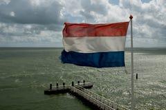 Wellenartig bewegende holländische Markierungsfahne Stockfotografie