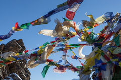Wellenartig bewegende mehrfarbige buddhistische Gebetsflaggen an Stockbilder