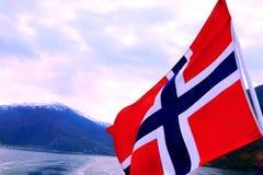 Wellenartig bewegende norwegische Flagge auf dem Fjord umgeben durch Gebirgshintergrund stockfotos