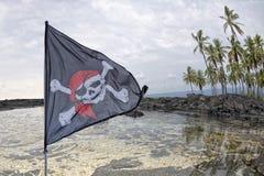 Wellenartig bewegende Piratenflagge lustiger Roger auf Tropeninselhintergrund Lizenzfreie Stockbilder